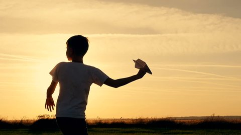 Happy guy playing with a paper airplane in a field in the sun. Silhouette at sunset