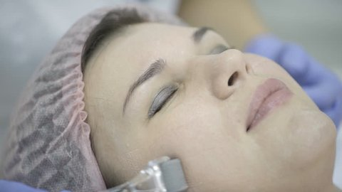 Specialist makes a woman with closed eyes with a Dermaroller, mesoroller, meso-roller, mesopen roller process. On the female skin of face beautician applies a cream for rejuvenation and purification