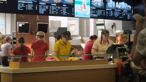 Moscow, Russia - September 16, 2017: The manager in McDonald's checks a check and issues an order to the client. McDonald's employees perform different tasks