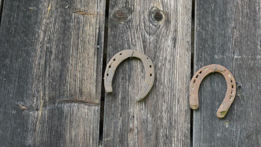 Hand hang retro rusty horse shoe on rural house wall.