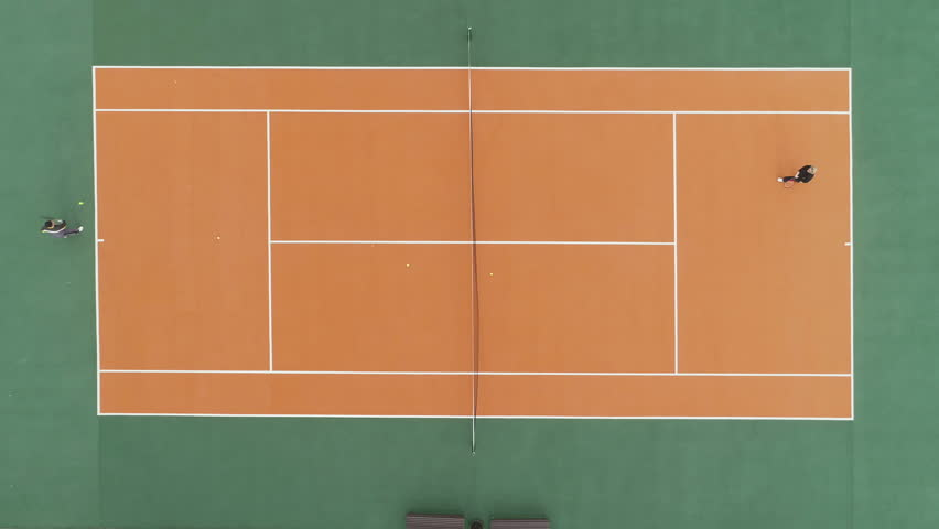 Players are playing tennis on green and orange court. Aerial vertical top shot. Drone is hovering. | Shutterstock HD Video #31742281