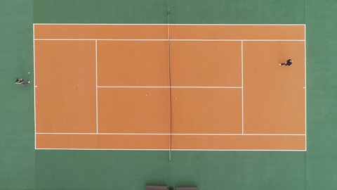 Players are playing tennis on green and orange court. Aerial vertical top shot. Drone is hovering.