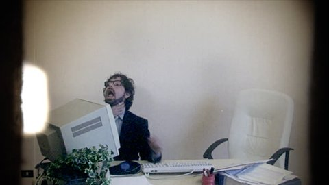 Fake 8mm amateur film: an office worker at work, getting strangled by a hand coming out of the monitor. Rebellion, oppression, workplace, fun.