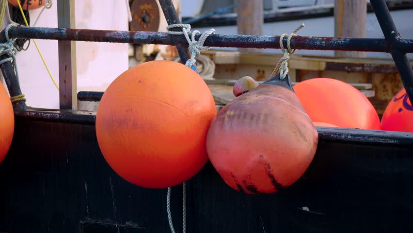 Commercial fishing boat in harbor. Giant orange floats having from side.