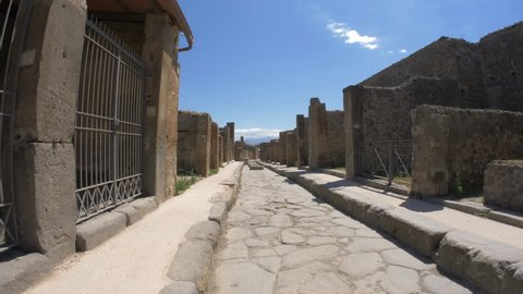 Narrow street of ancient Pompeii are paved with cobblestones with huge stones lying in the middle.