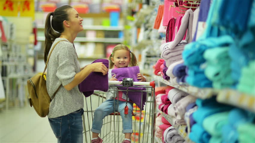 Indoors Portrait of Happy Female Child and Her Attractive Mother in Hypermarket Choosing Violet Towel Together Standing near Supermarket Shelf. | Shutterstock HD Video #31771501