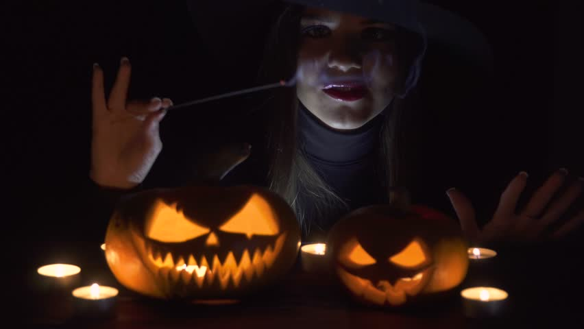 Halloween Witch with a magic Pumpkin. Beautiful young woman in witches hat and costume holding carved pumpkin. Halloween art design