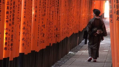 KYOTO, JAPAN - 22 OCTOBER 2012: A woman in Japanese geisha clothing walks through torii gates at Fushimi Inari in Kyoto, Japan