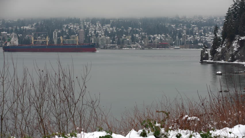 English Bay Snow and Freighter 4K. UHD. A freighter travels into Burrard Inlet from English Bay. In the background is West Vancouver. Vancouver, British Columbia, Canada. 4K. UHD.