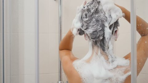 Woman washes long hair with shampoo in shower cabin