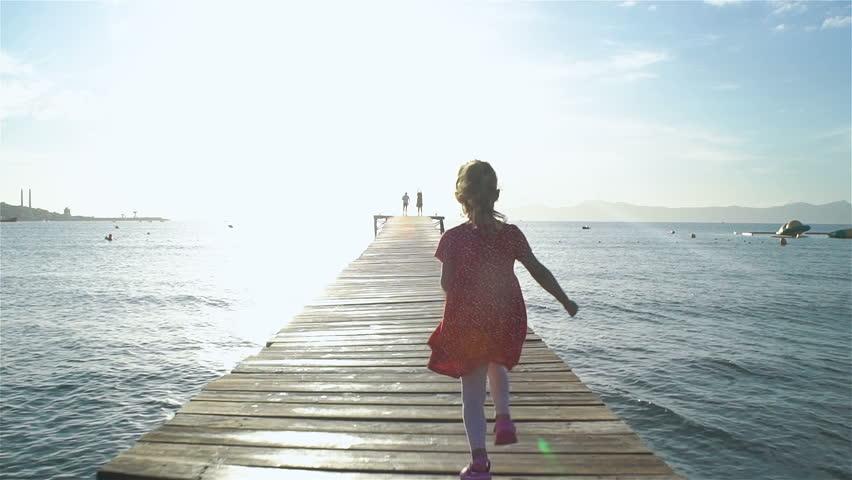 Little girl wearing red dress runs on wooden sea pier towards the rising sun