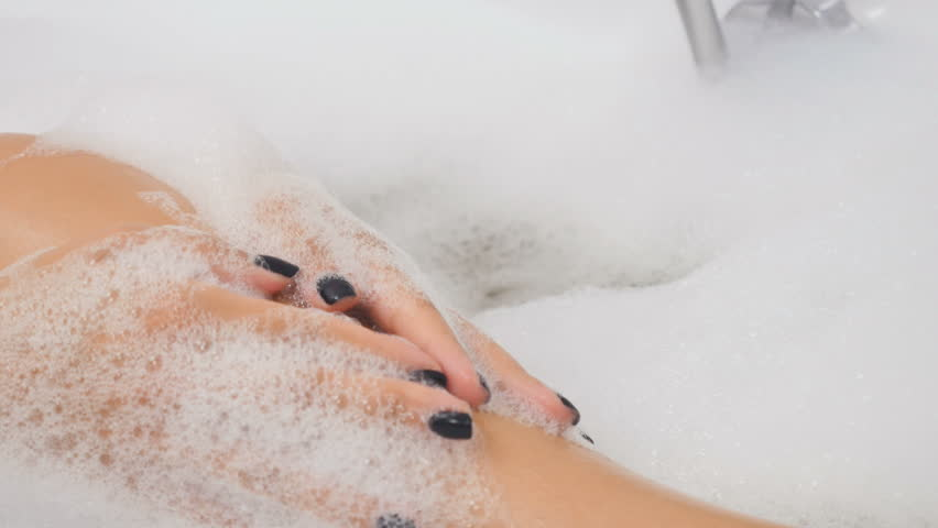Woman massages leg with foam in the bath