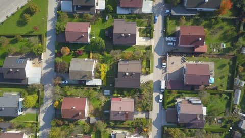AERIAL TOP DOWN Flying over red rooftops in idyllic suburban town on sunny autumn day. Row houses with green garden lawns and narrow empty roads in peaceful suburbia. Perfect homes in quiet suburbia