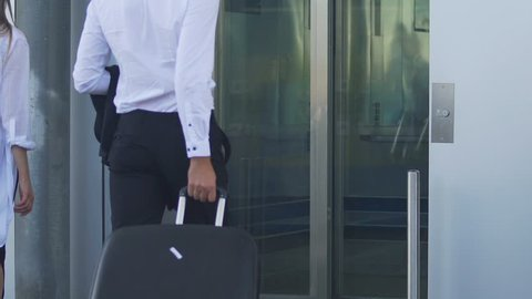 Man and woman approaching elevator doors, entering lift, male carrying suitcase