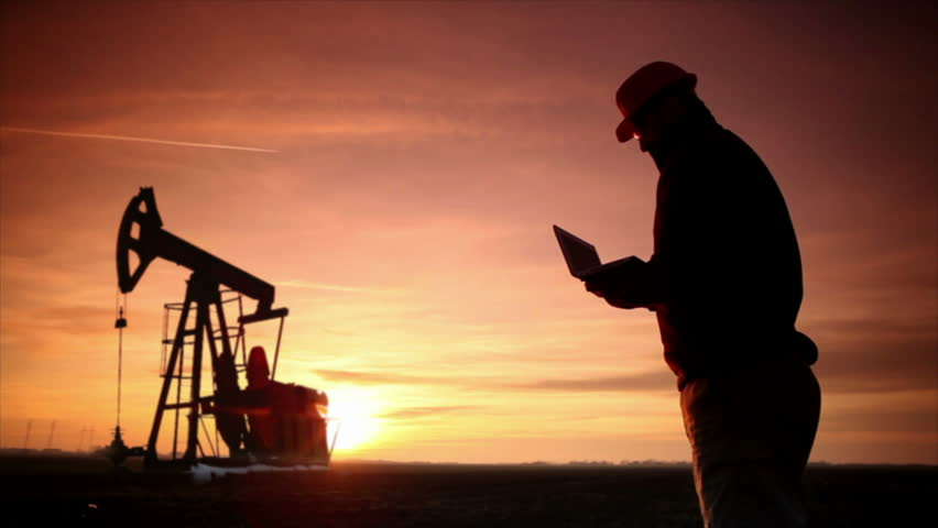 Oil Industry Pumpjack with one oil worker who using a phone and typing on laptop.In a background is Silhouette of one Pump jack at sunset light.