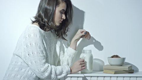 Cinemagraph of young brunette woman in white woolen sweater sitting at kitchen table and holding dunked cookie above glass jar with milk