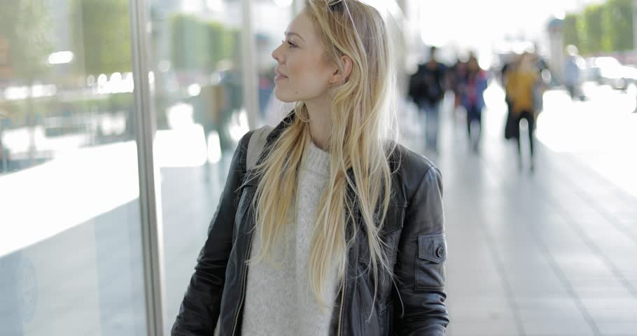 Beautiful young woman walking near shop and looking with interest at shop-window while looking for new clothes. | Shutterstock HD Video #31880041