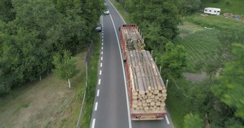 Aerial view of Truck Carrying Lumber. Double length log truck driving on a mountain road.