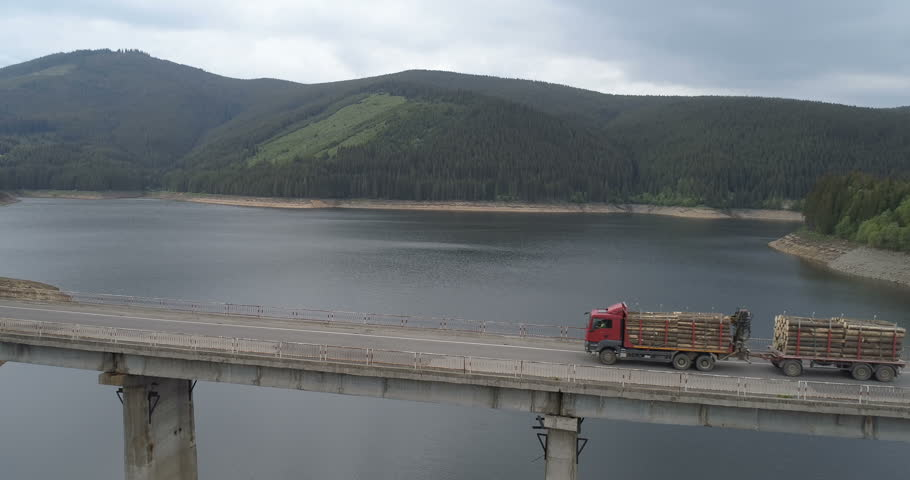 Aerial view of Truck Carrying Lumber. Double length log truck driving on a mountain road
