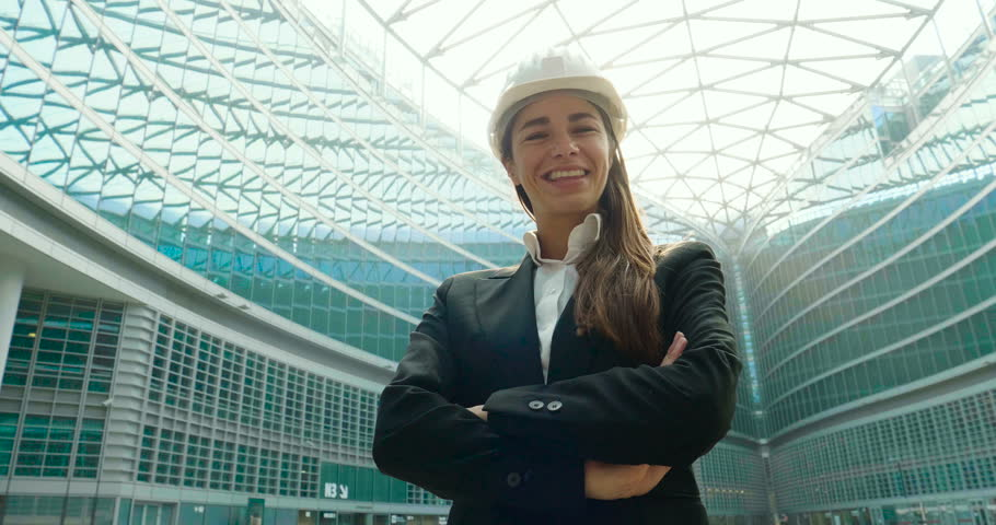 Portrait of a female engineer smiling while looking at camera and in the background you can see the skyscrapers she designed.