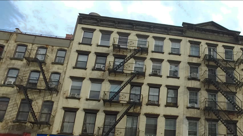 Establishing shot of typical New York City style apartment building exterior day time HD stock video. Dutch angle cant tilt perspective view of windows and fire escape on facade