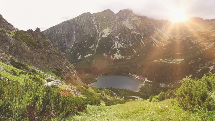 Tatry mountains in Poland. Panorama of mountain range, lake and green grass motion on wind. Summer nature landscape. Beauty world, sport lifestyle, holidays, travel and recreation. Full HD