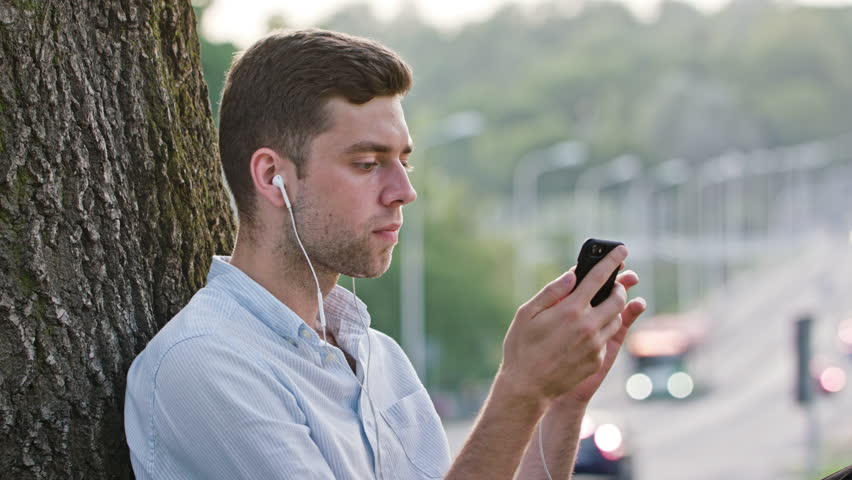 A young man using a mobile and sitting under the tree. Closeup shot. Soft focus. | Shutterstock HD Video #31917391