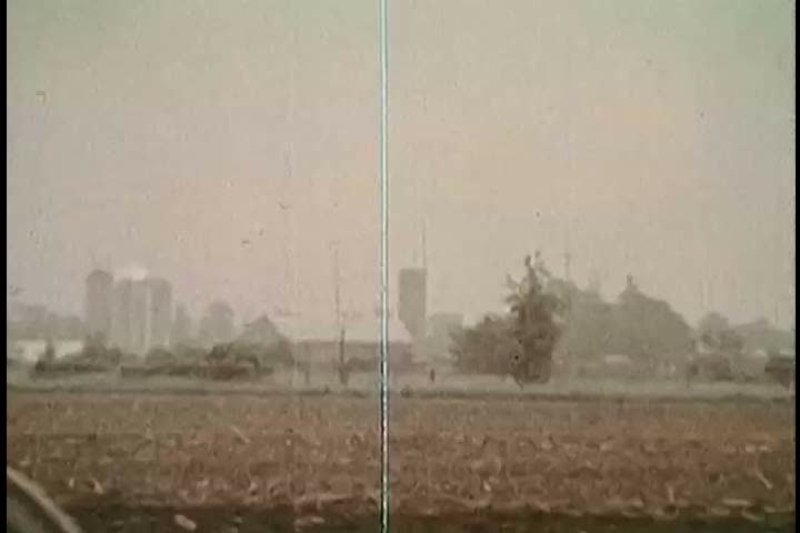 CIRCA 1970s - Skies darkening above a farmer on a tractor, rainfall, flooding and a boy sailing a toy sailboat on a lake are shown, in 1972. | Shutterstock HD Video #31922041