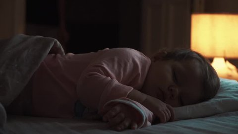 Mother enters the room. sleeping baby happy and carefree, the mother caresses kiss goodnight.