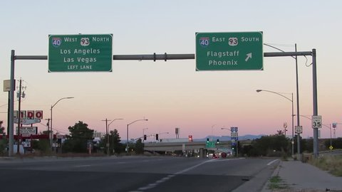 Traffic passes interstate 40 east and west signs on historic us route 66  highway near sunset in kingman northern arizona, usa