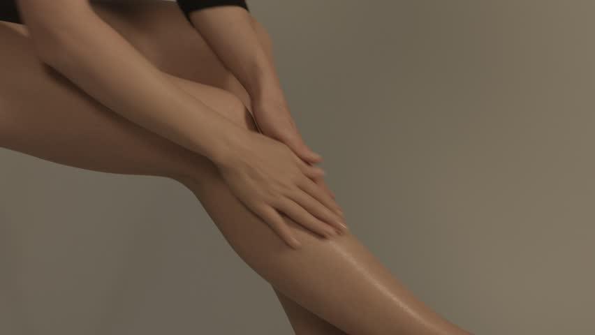 Beautiful female legs overgrey background.