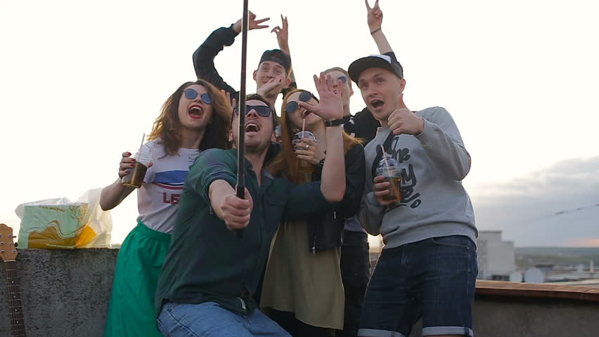A group of young active friends makes a cool selfie on the roof of the house