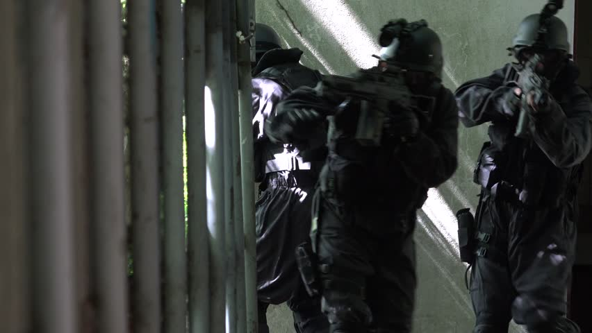 A Special Force Team walk in a open corridor.