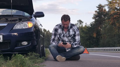 Caucasian young man sitting roadside near broken car. Guy using smartphone texting message or calling