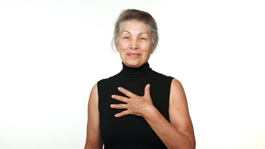 elder serene woman with white tied hair looking at camera smiling with hand on chest thanking over white background in slowmotion. Concept of emotions