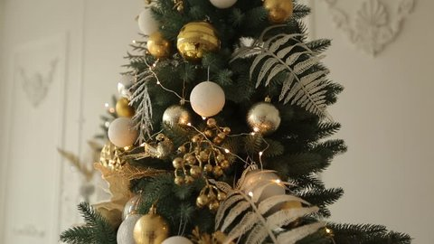 Stylish white christmas interior with decorated fir trees. Comfort home with christmas tree full of golden decorations, with wreath and lights of garlands on background. New Year's Eve.