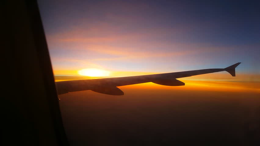 AERIAL, CLOSE UP: Looking out the airplane window while flying above dense clouds into dreamy romantic golden light sunset. People traveling with a jetliner at sunrise. Detail of an aircraft wing
