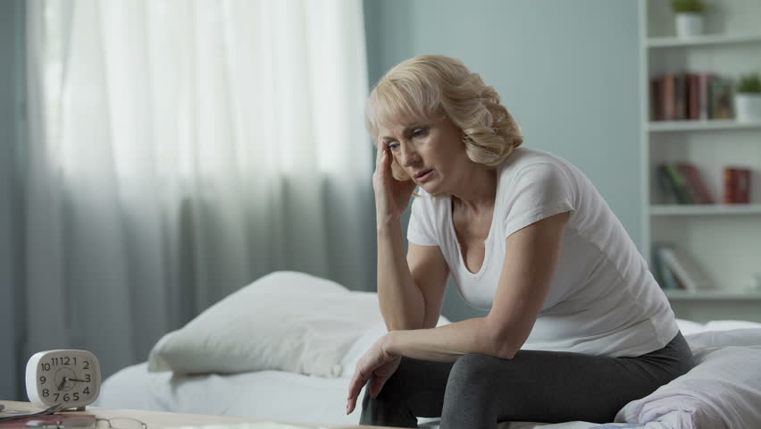Menopause. Adult female sitting on bed and suffering from migraine, health