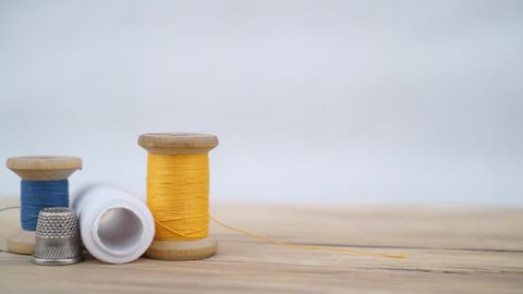 Moving footage from slider of old spool of thread with needle and sewing thimble. Sewing background. Tailor's work table.
