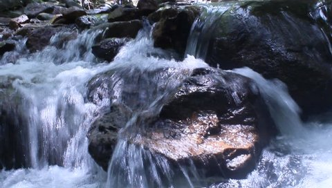 close up to a small waterfall in a forest. Beautiful small tourist waterfall. a small lake into which falls a waterfall.Relaxation On a hot day. Keep cool and happy