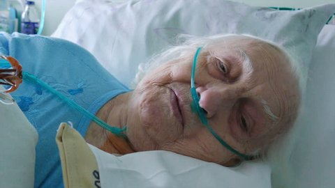 Old woman is recovering after heart surgery in hospital bed