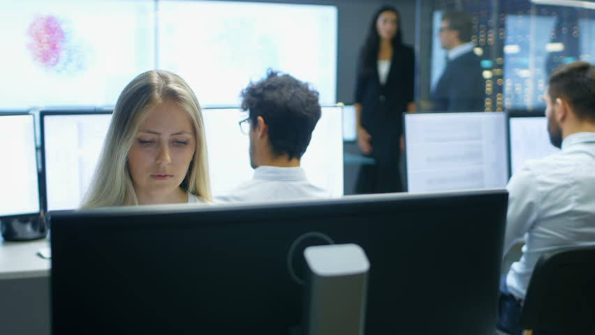 Female Computer Engineer Works on a Neural Network/ Artificial Intelligence Project with Her Multi-Ethnic Team of Specialist. Office Has Multiple Screens Showing 3D Visualization. 4K UHD.