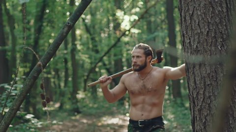 Portrait of handsome bearded man with ax in the forest. Slowly