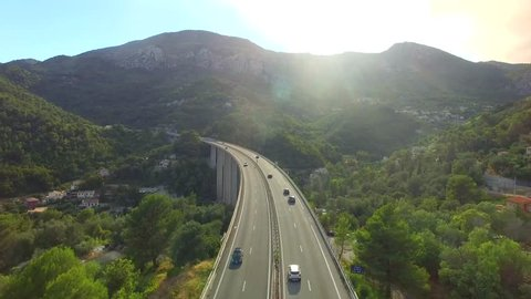 Cars move at highway bridge road in mountains above valley village morning aerial 4k. Fly above traffic on bypass over hill town Europe sun shine. Motorway vehicles pass scenic Italian Alps landscape