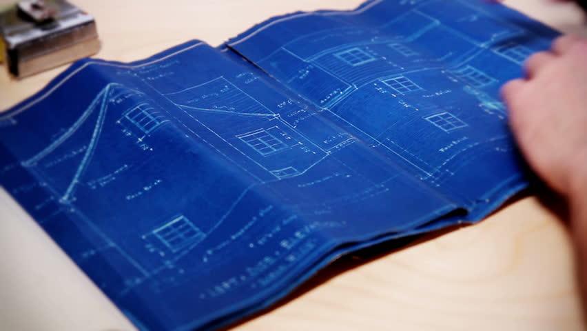 A carpenter examines a house's blueprints.