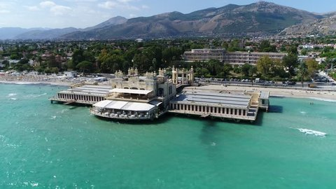 Aerial view showing Mondello coast showing the beach and large building in middle Mondello is small borough of city of Palermo in autonomous region of Sicily in Southern Italy Azure blue water 4k