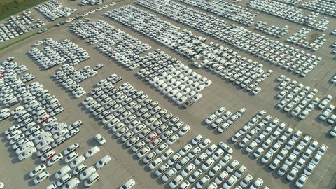 AERIAL: Flying over big industrial zone with big parking lot of brand new cars. Many white cars waiting for sale and transportation at big sea port parking space. Automobile industry.