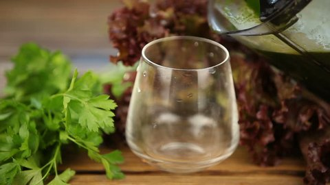 parsley and celery juice in glass on a wooden table