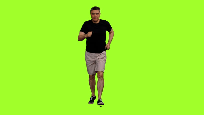 Front view of adult man in shorts and black t shirt jogging on green screen background, Chroma key, 4k footage
