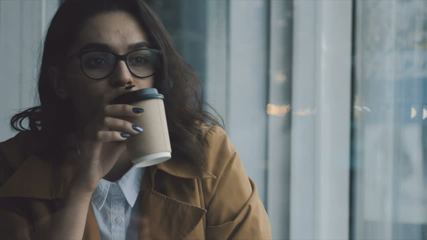 Young woman having coffee at the cafe | Shutterstock HD Video #32109001